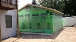 With the walls up, the trusses on, and the roof sheeting complete, the garage is wrapped to protect it from the elements until it is sided.
